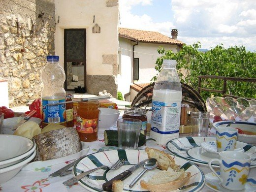 Richard Kelland: This is the house where we stayed in Italy. In the foreground you can see breakfast, and in the background is the house. The leafy thing between the two is a fig tree.