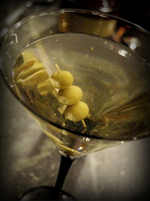 A great recipe for a dirty martini with garlic cheese stuffed olives.