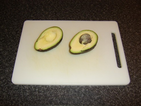 The avocado is now halved with the stone embedded in one half
