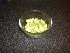 The peeled avocado halves are chopped and added to a mixing bowl