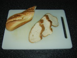 French stick is sliced at an angle to create bread slices for bruschetta