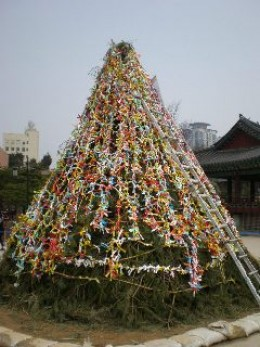the rope with ribbons of wish is then up to a pile of wood, a structure that looks like wishing tree