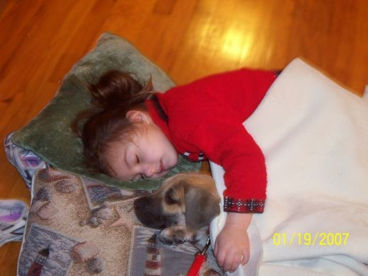 My granddaughter agrees that happiness is a warm puppy!