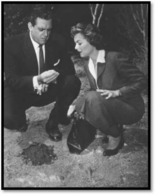 PERRY MASON (LEFT) AND DELLA STREET LOOK AT A PIECE OF CRUCIAL EVIDENCE THEY NEED TO HELP GET THEIR CLIENT SET FREE.