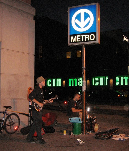 The Metro at night with street musicians.