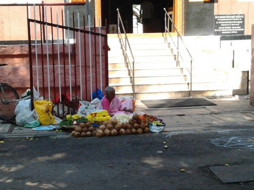 A woman sits outside a temple selling coconuts,flowers,lemons, betel leaves and nuts all required for the poojas inside. So, if  you forget to take them with you, you can buy right outside the temple.