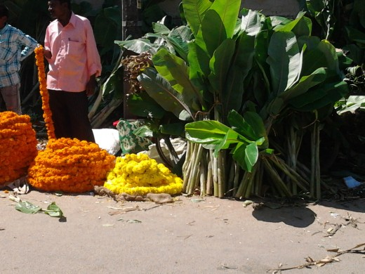 Large bundles of  marigolds and chrysanthemums strung together are sold in lengths. Popularly used to decorate pooja rooms of homes and temples. Dieties are often garlanded with such flowers. Plantainstems with leaves in tact  to adorn poojarooms.