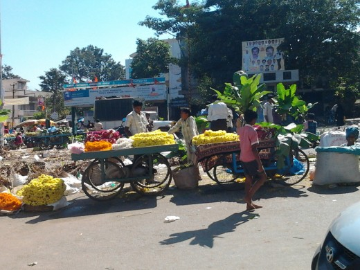 A market square with pushcart vendors selling fruits, flowers and banana stem with leaves.
