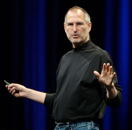 Steve Jobs speaking at one of his conferences with his famous look - black turtleneck  shirt and jeans.