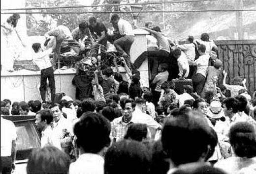 Marines throwing Vietnamese back over the American Embassy wall, Saigon, R. South Vietnam
