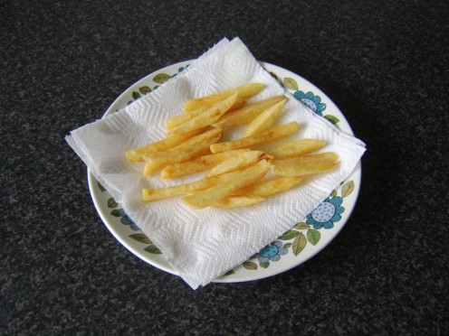 The fries are drained on kitchen paper after their final deep fry