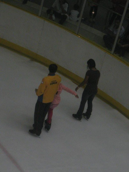 Ice skating coach teaching his student