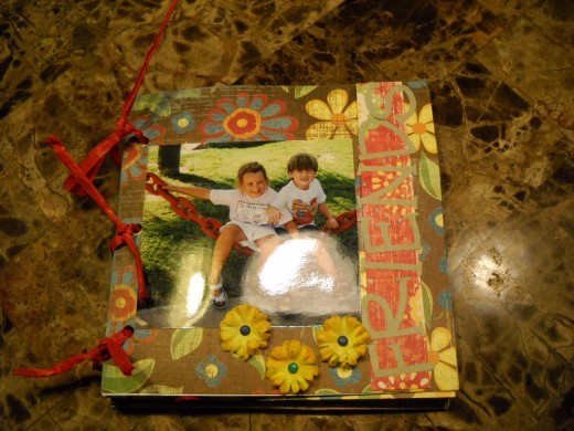 Scrapbook made with cardboard covers and double-sided paper pages.