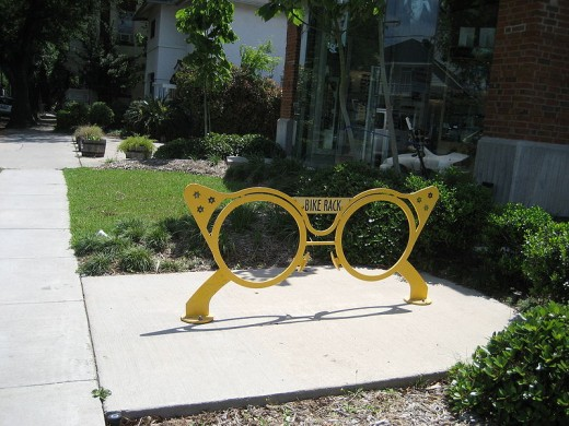 A bike rack shaped like a pair of eyeglasses located on St. Charles Avenue, in New Orleans, in front of an eyeglasses store.