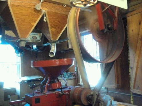 Grist mill machinery grinding meal.