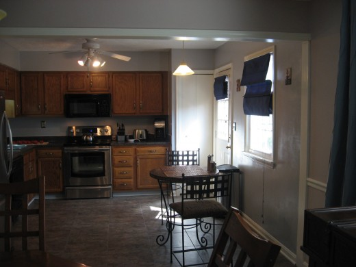 View of kitchen after paint, curtains, and flooring