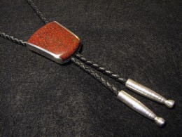 A very traditional bolo tie made with braided leather. Note the sterling silver aguillettes and dinosaur bone inlay on the decorative slide.