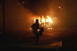 A man runs over a fence in front of a van set ablaze by a group of rioters.