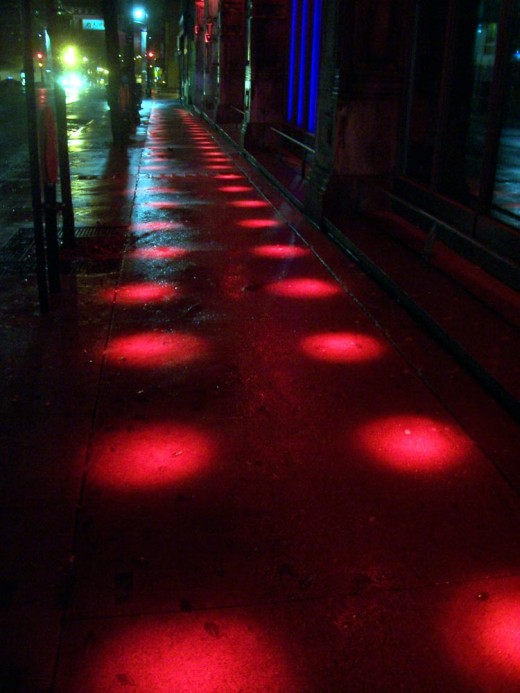 Lights reflected on a wet Montreal sidewalk