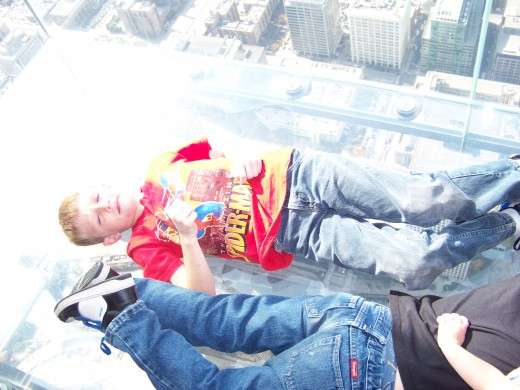 My boys lying down on clear Sky Deck on Willis Tower.