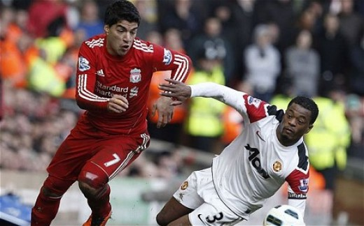 Uis Suarez of Liverpool FC overpowers Patrice Evra of Manchester United