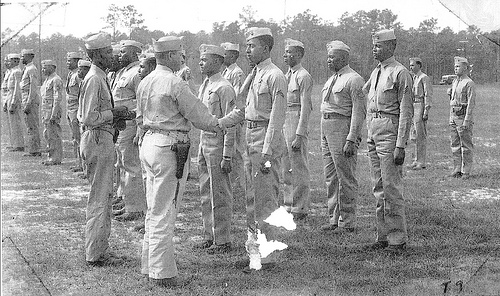 Lt. Col. Frazier, Commanding Officer, Montford Point Camp, presents WWII Victory Medal to members of the Montford Point Camp, and the 51st, and 52nd Defense Battalions.  From the collection of Joseph H. Carpenter.