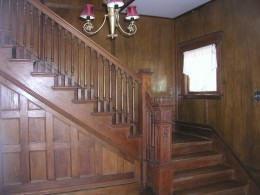 Beautiful Walnut and Pine staircase.  the area beneath the stairway actually opens wide for storage.