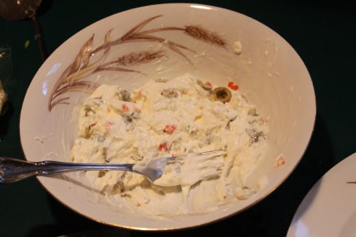 the stuffing of cream cheese and green olives all mixed up in a bowl