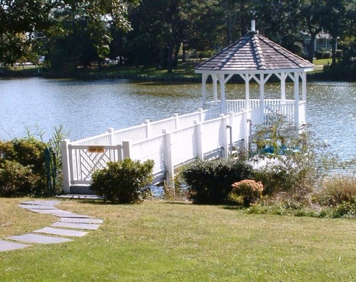 Example of gazebo with winding pathway leading to it and a lovely garden beside the entry gate.