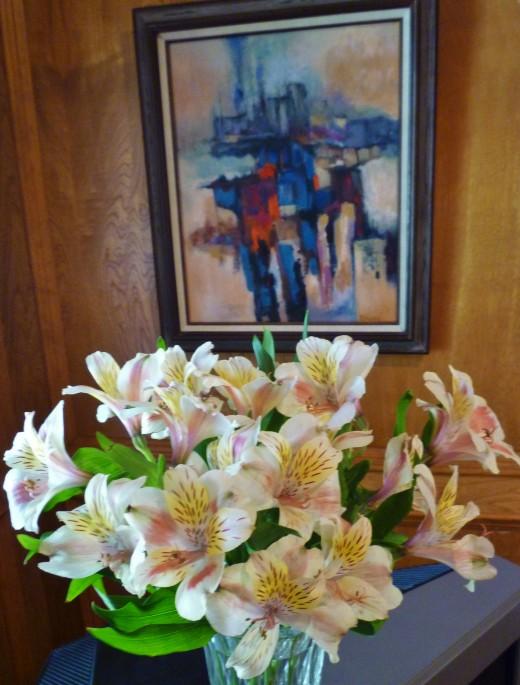 Dr. Robert Rogan painting on wall behind vase of alstroemeria flowers.