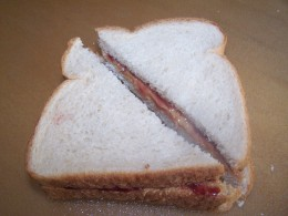 Cut the square sandwich in half to create two triangle halves.