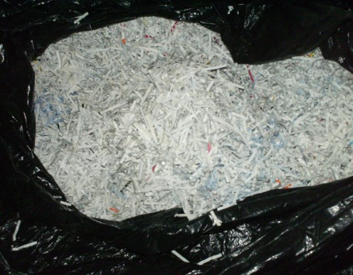 Large black trash bag filled with shredded paper.