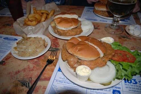 As big as a plate. Served with dill pickles, raw onion, and German Potatoes. Some diners like sliced tomatoes and mayo.