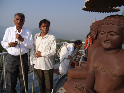 Author ( the person on the right) near the Mahaveera statue at the top of the memorial built on the hill where Lord Mahaveera delivered his first preaching