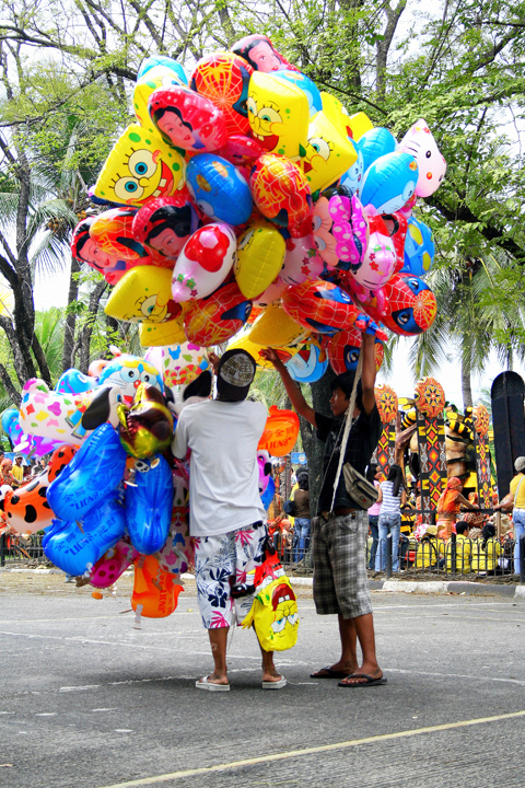 Balloon vendors trying to untangle their wares