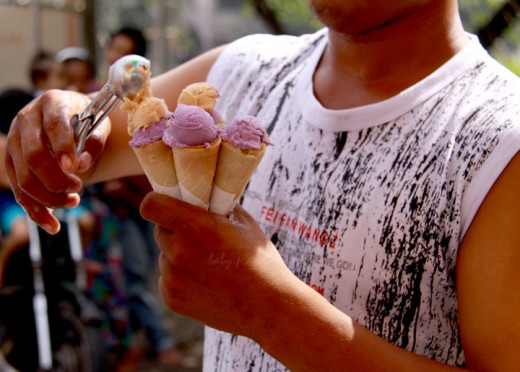 ice cream vendor filling up several cones at a time while children wait behind him