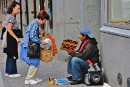 Two kind women helping a homeless man in New York, handing a meal to him.