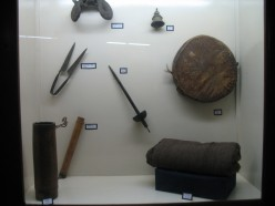 THERE IS A LONG TUBE,A DIVIDER,A EAR PROTECTOR,A BELL,A SWORD,A ROUND PILLOW AND A SUIT CASE KEPT IN CLOCK WISE DIRECTION.NO INFO IN MUSEUM.NO GUIDE.