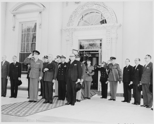 Prince Charles of Belgium and President Truman and other dignitaries stand at attention in the entranceway to the White House, 1948
