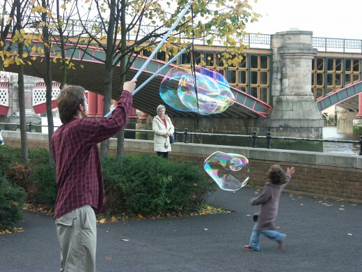 man making huge bubbles and kids loving it.