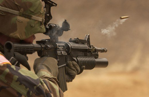 A U.S Army soldier firing the M4A1 with underslung M203 grenade launcher attachment