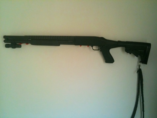 Mossberg 500 with shortened barrel, pistol grip with telescoping stock and hand weaved paracord sling.