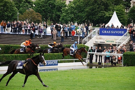 Jockeys negotiate a fence with water on the other side at The Grand Steeple de Paris