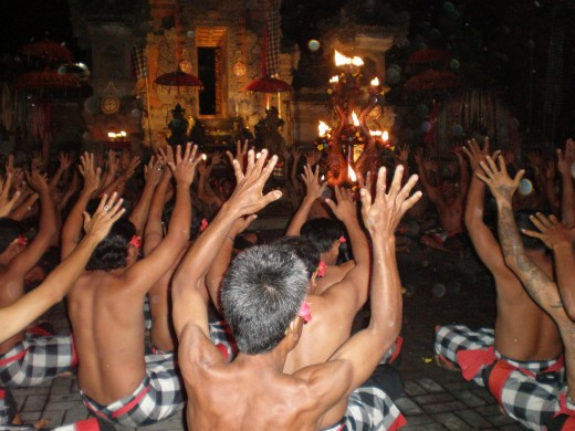 Choir dancing to the rhythmic sound of their own voices, their hands raised to the sky and bodies shaking in unison. Ubud, Bali, Indonesia.