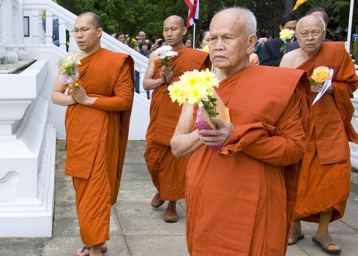 Monks parading in the temple with flowers in hand