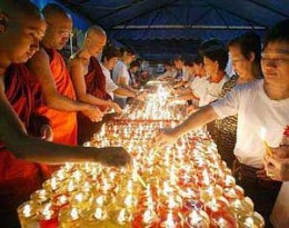 Buddhists light candles as offering for Buddha