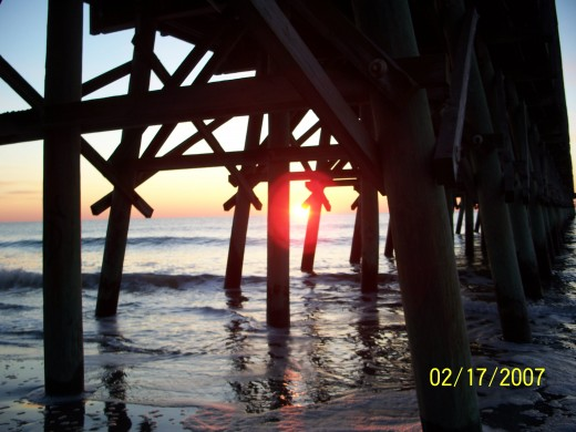 PICTURE OF SUNRISE AT MYRTLE BEACH  UNDER THE PIER PILINGS