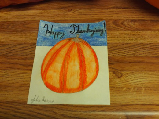 Coloring in the blue sky above the pumpkin, and adding the text to the illustration.