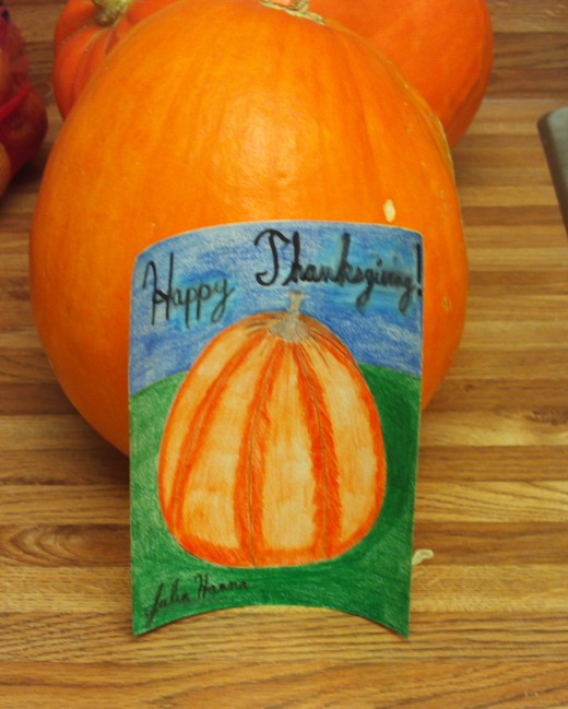 The completed drawing resting against the pumpkin.