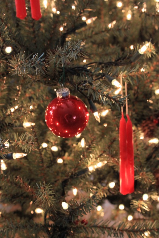 a clsoe up of christmas tree lights, ornament and candle